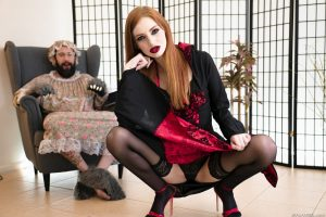 Sexy redhead with red lips Maya Kendrick crosses stocking clad legs in heels