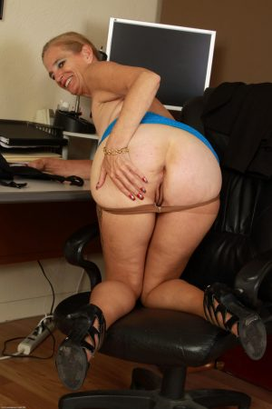 Mature lady casts asides business clothes and hose in her home office