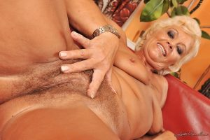 Blonde granny stripping off her clothes and exposing her bushy cunt