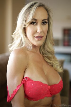 MILF Julia Ann stripping down naked on the couch and showing her fake tits