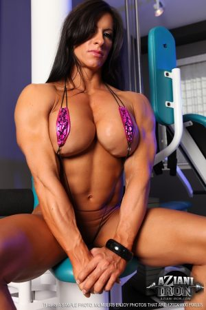 Brunette female Angela Salvagno shows off her muscles and big boobs in gym