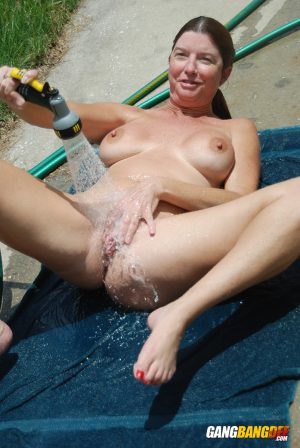 Mature redhead Dee Delmar wets her big tits and twat with hose on concrete pad