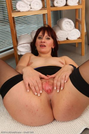 Mature redhead Vera Delight fingers her wide open snatch in sheer stockings