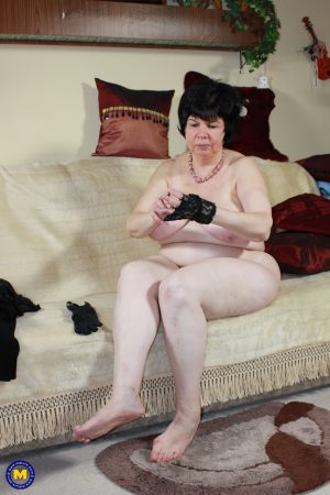 Raven-haired granny Eva unleashing her big tits and toying her mature cunt