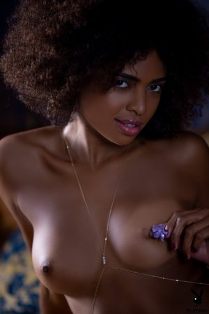 Ebony centerfold model Bruna Rocha poses topless in a thong upon a bed