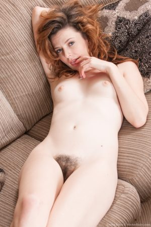 Sexy redhead Emma Evins removes her pink bodysuit to reveal super hairy muff