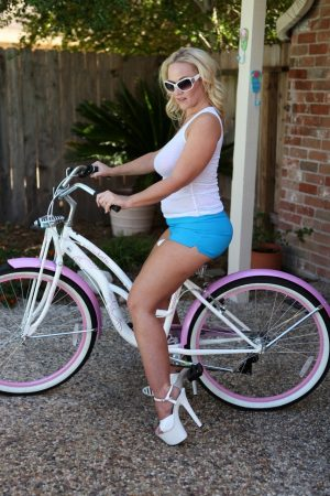 Blonde BBW Dee Siren hows her big butt in booty shorts atop a bicycle