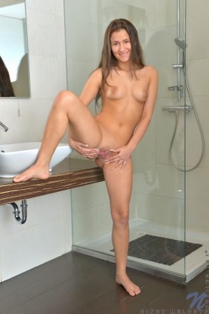 Solo girl Cindy Melody holds her bare ass while showing her twat in a bathroom