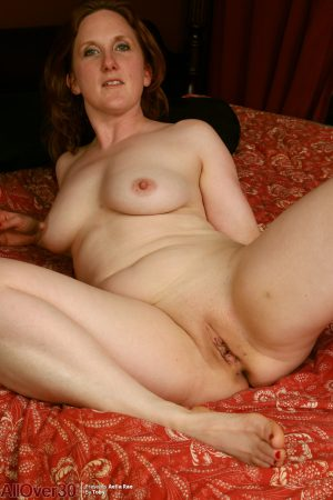 Thick over 30 redhead Aella Rae doffs underthings before masturbating on a bed