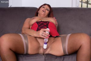 Mature redhead Beau Diamonds toys her pussy in a girdle and nylons on a couch