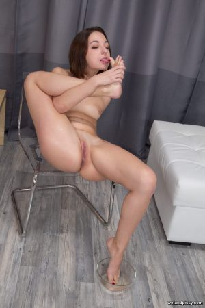 Petite brunette Leona wets herself, strips and masturbates in the chair