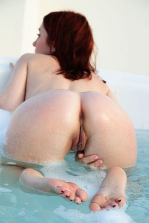 Petite redhead Night A strikes tempting nude poses as she gets in the water