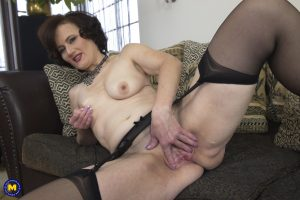 Brunette granny Alice S strips to lingerie and plays with a red sex toy