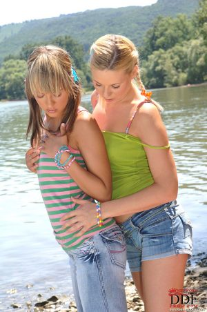 Young lesbians Blue Angel & Yasmine Gold lick pussies on gravel beach