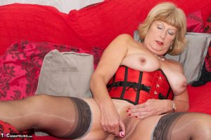 Mature woman with blonde hair wears a waist cincher while rubbing her pussy