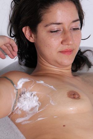 Brunette MILF Miranda teases with her hairy armpits and twat in a foamy bath