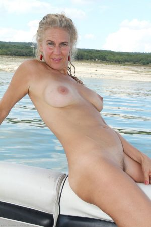 Mature blonde Sabrina P removes her swimsuit on a boat and masturbates