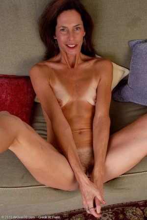 Skinny mature lady spreading and toying her hairy pussy with a glass dildo
