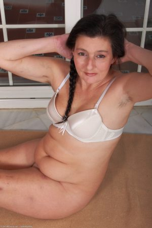 Pigtailed MILF Becky shows her natural tits and hairy twat on the floor