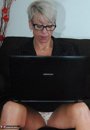 Mature lady Shazzy B sports short hair while exposing her upskirt underwear