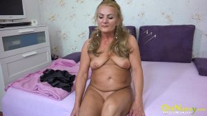 Amateur granny Valdi exposes her curves and toys her twat on a bed