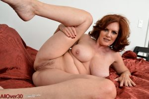 Natural redhead Andi James bares saggy tits & spreads vagina to finger fuck