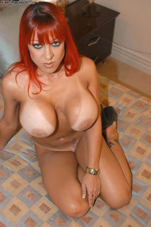 Captivating redhead MILF Whitney Wonders flashes her super big tits on bed