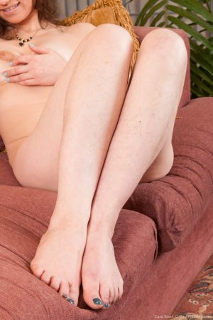 Naughty brunette Cara Banx spreading her very hairy pussy on a couch