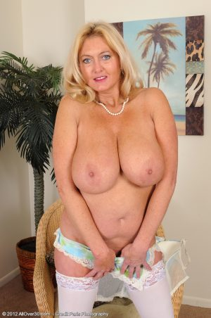 Mature blonde Tahnee Taylor bares huge tits before crossing stocking clad legs