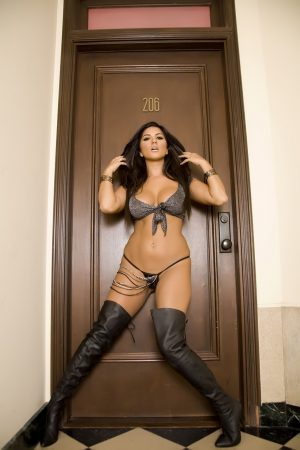 Hot Indian MILF Sunny Leone poses in her top & high boots in front of her door