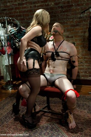 Lusty domme Aiden Starr masturbates while giving a handjob to a tied up guy
