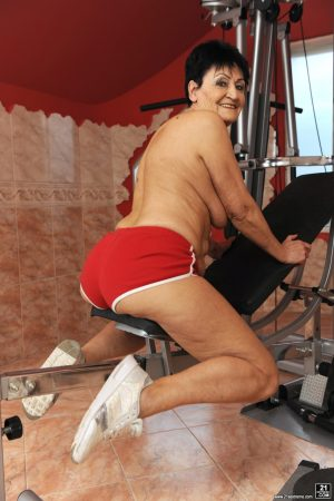 Sassy granny Anastasia strips at the gym to spread naked on the equipment