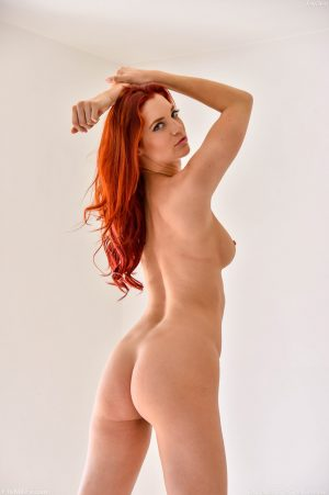 Sexy redhead with nice tits attends to her horny pussy with glass dildo
