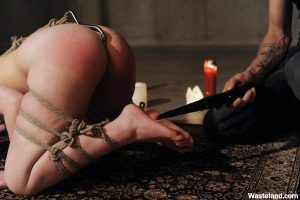 Submissive female is subdued with rope and anal hook before a spanking