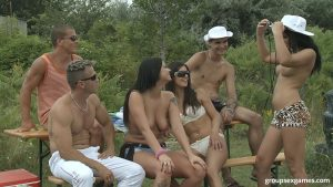 Open minded couples engage in group sex games on a secluded sporting field