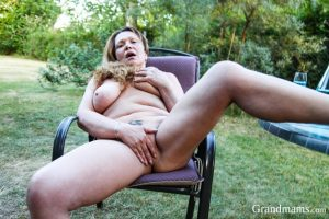 Busty mature blonde stripping in the back yard and fingering her vagina