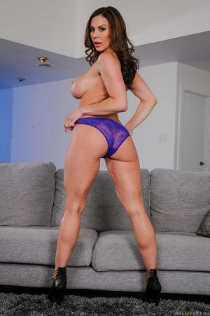 Mature brunette Kendra Lust strips her clothes to bare big fake tits & bum