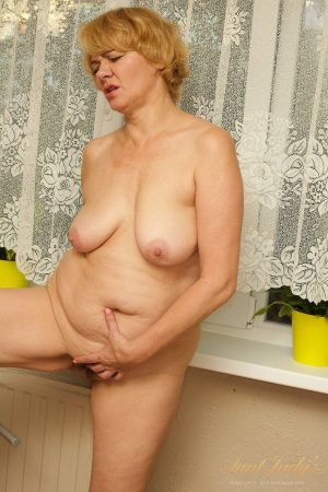 Mature granny Aliona strips her dress and rubs her hairy muff in the kitchen