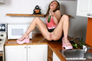 Blond solo girl toys her twat with a cucumber on counter top until she squirts