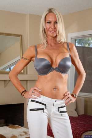 Slender busty cougar Emma Starr strips to high heels to show big fake tits