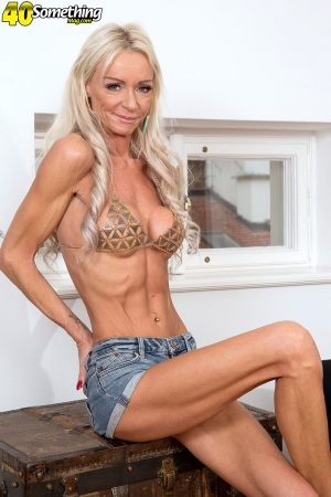 Skinny platinum blonde cougar Alexis Starr disrobes to high heels on a sofa