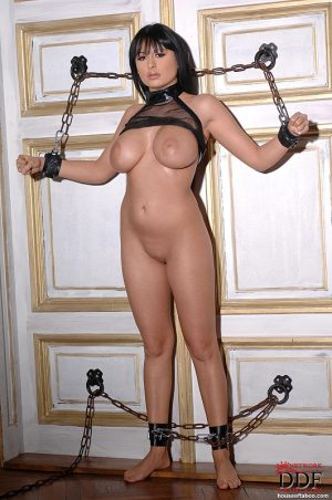 Chesty fetish model in chains receiving bare ass spanking and whipping