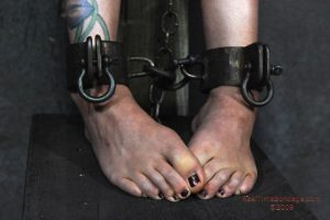 Tattooed blonde Rain Degrey is restrained for lezdom sex in a dungeon