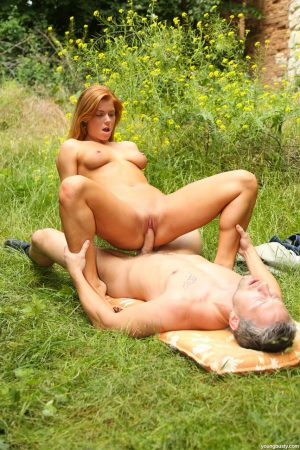 Horny redhead slut entices a stranger to naked ass licking in a grassy field