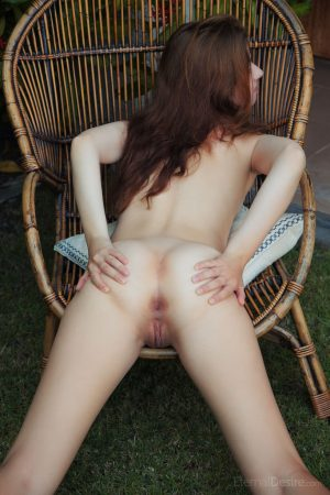 Totally naked redhead Sienna grabs her tight ass while on a patio chair