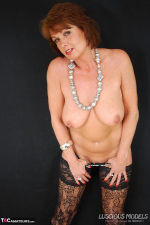 Mature redhead peels off her underwear while showing her great boobs