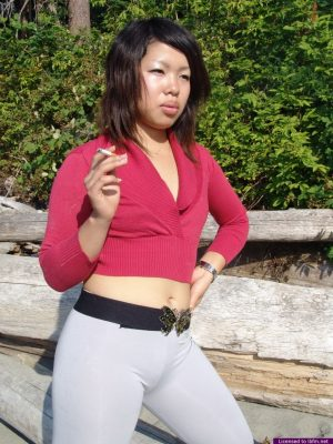 Asian amateur Sugar slips spandex pants over her ass while smoking on a beach