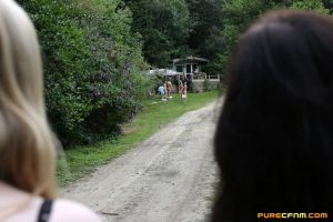 Lovely clothed female students blow off a nudist colony outdoors