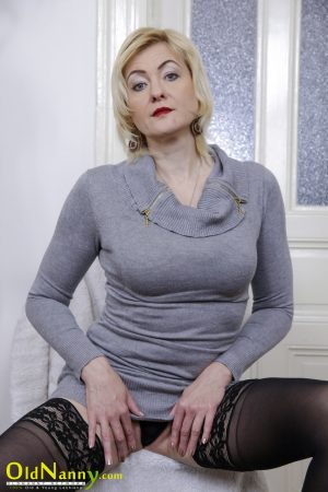 Mature blonde Penny Priet exposes her big tits and toys her cunt in stockings