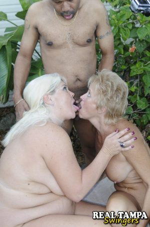 Naked mature women kiss while giving a black man a blowjob in the garden